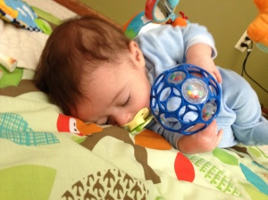 """Uncle Miguel bought Lucas an """"Oball"""" that he loooooooves.  In fact, he loves it so much that he plays with it, sleeps with it, and we had to find a way to attach it to his car seat so he can travel with it.  If we ever loose this, we're in trouble"""